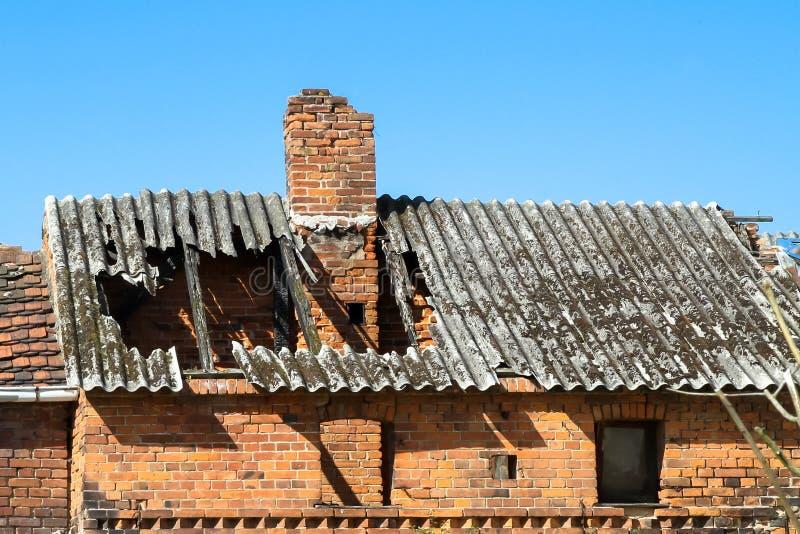Ruínas da casa velha abandonada com o telhado e a chaminé de queda danificados no dia ensolarado com o céu azul claro imagens de stock royalty free