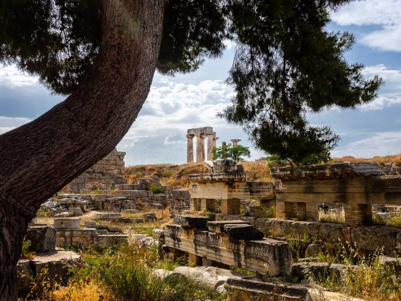 Ruínas da cidade antiga de Corinth e do templo do tiro de Apollo no dia sereno fotografia de stock royalty free