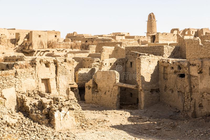 Ruínas da cidade velha do Oriente Médio antiga construída de tijolos da lama, mesquita velha, minarete Al Qasr, oásis de Dakhla,  imagens de stock royalty free