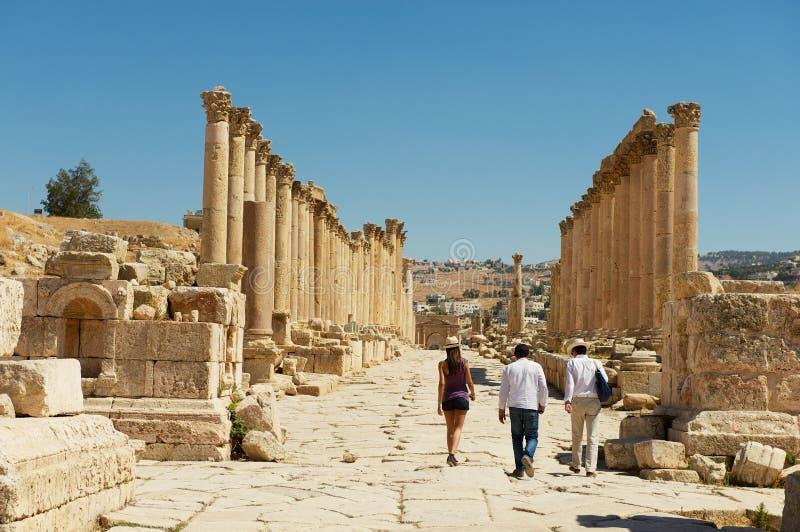Ruínas da visita dos turistas da rua da colunata na cidade romana antiga de Gerasa Jerash moderno em Jordânia foto de stock