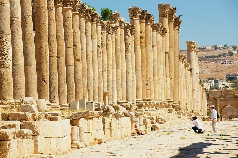 Ruínas da visita dos turistas da rua da colunata na cidade romana antiga de Gerasa Jerash moderno em Jordânia fotografia de stock