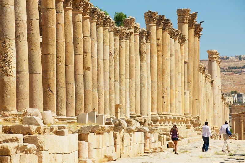 Ruínas da visita dos turistas da rua da colunata na cidade romana antiga de Gerasa Jerash moderno em Jordânia fotografia de stock royalty free