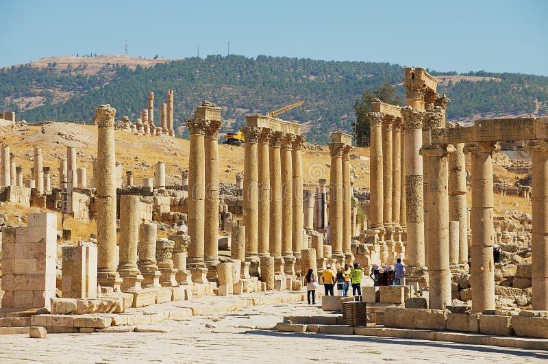 Ruínas da visita dos turistas da rua da colunata na cidade romana antiga de Gerasa Jerash moderno em Jordânia imagens de stock royalty free