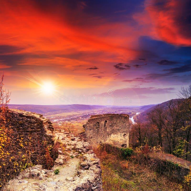 Ruínas de um castelo velho nas montanhas no por do sol foto de stock