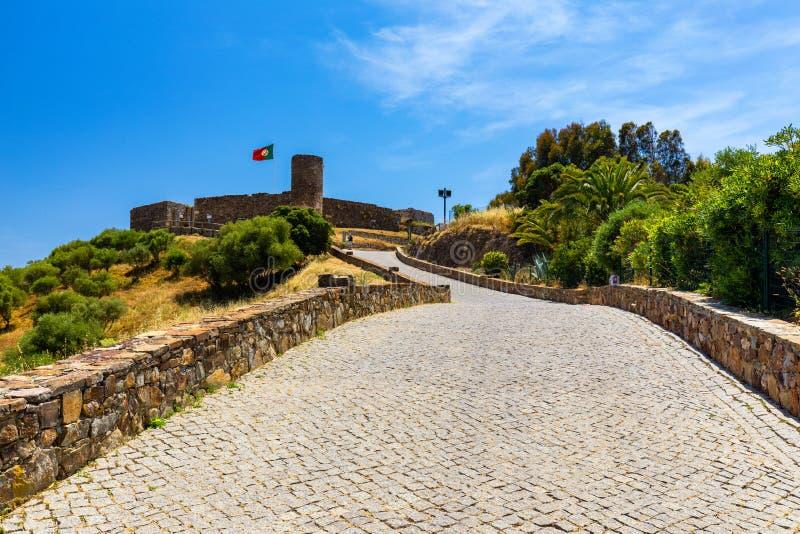 Ruínas do castelo em Aljezur com ondulação da bandeira portuguesa, o Algarve, Portugal O castelo de Aljezur, castelo lindo árabe  foto de stock royalty free