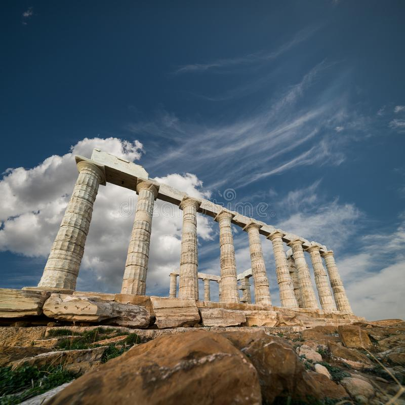 Ruínas do templo de Poseidon no cabo Sounio sob o céu azul, G imagem de stock