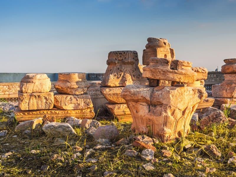 Ruïnes en delen van oude kolommen, capitels en basissen met Griekse en Christelijke symbolen in zonsonderganglicht stock foto