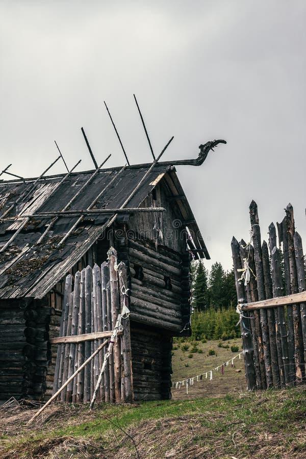 Ruïnes van een heg en een oud verlaten houten huis met dakversieringen stock foto's