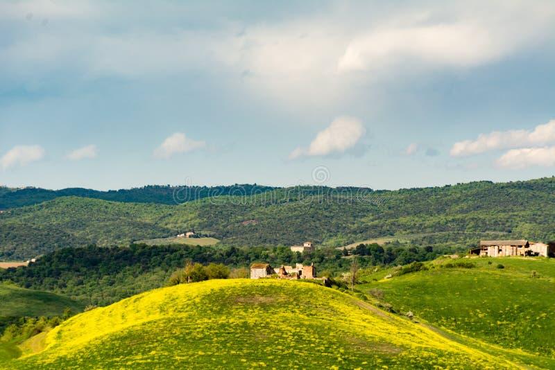 Ruïnes van een oud die huis bovenop een heuvel door gele stroom wordt omringd stock fotografie