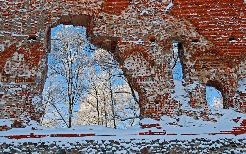 Ruïnes van het Viljandi-Ordekasteel in koude en zonnige de winterdag, door openingen in de muur kunnen wij ijzige bomen zien royalty-vrije stock afbeelding