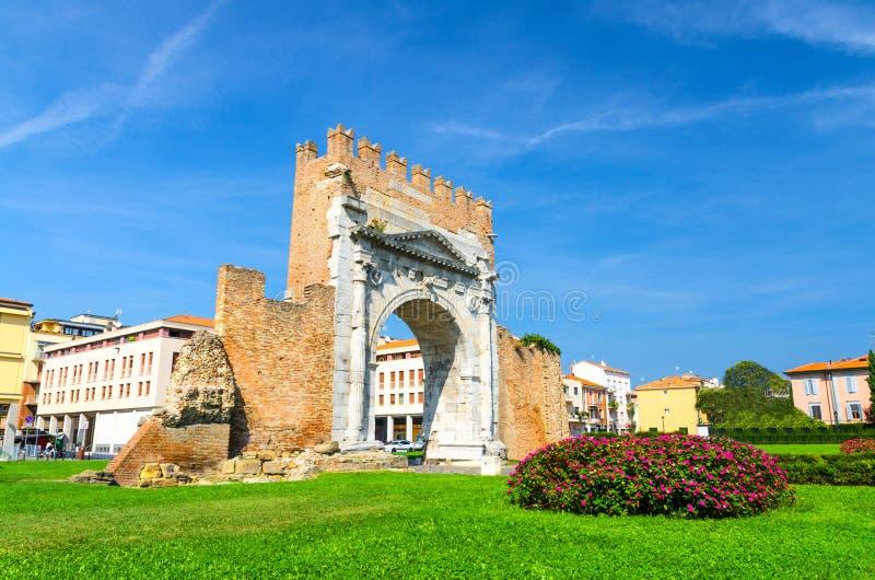 Ru?nes van oude bakstenen muur en steenpoortboog van Augustus Arco di Augusto, groen gazon met struik van bloemen in Rimini royalty-vrije stock foto's