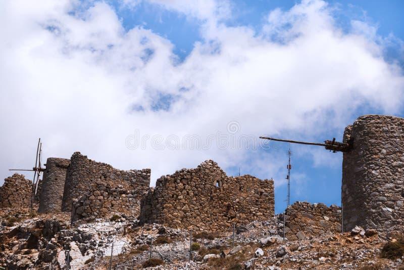 Ruïnes van oude windmolens op rotsachtige bergen met blauwe hemel met witte wolken stock afbeelding