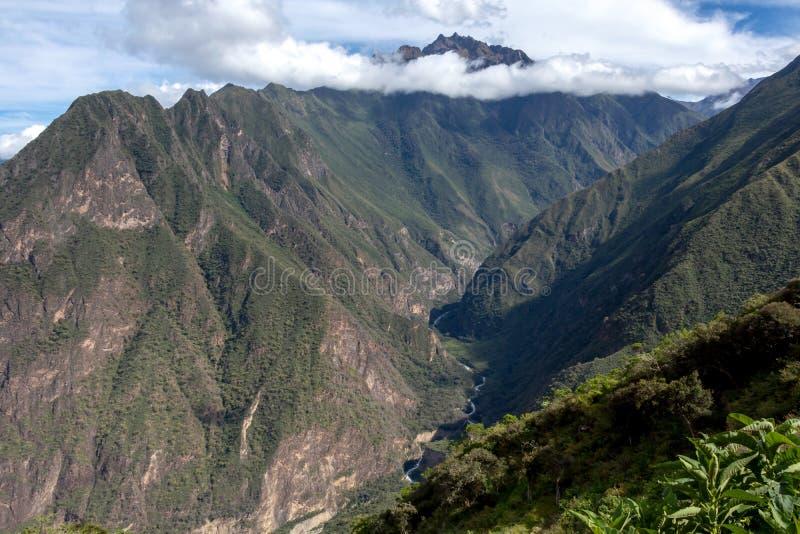 Ruïnes van Pinchinuyok bereikt de oude Inca die door berg worden omringd en wolken boven de groene canion in Peru een hoogtepunt stock foto