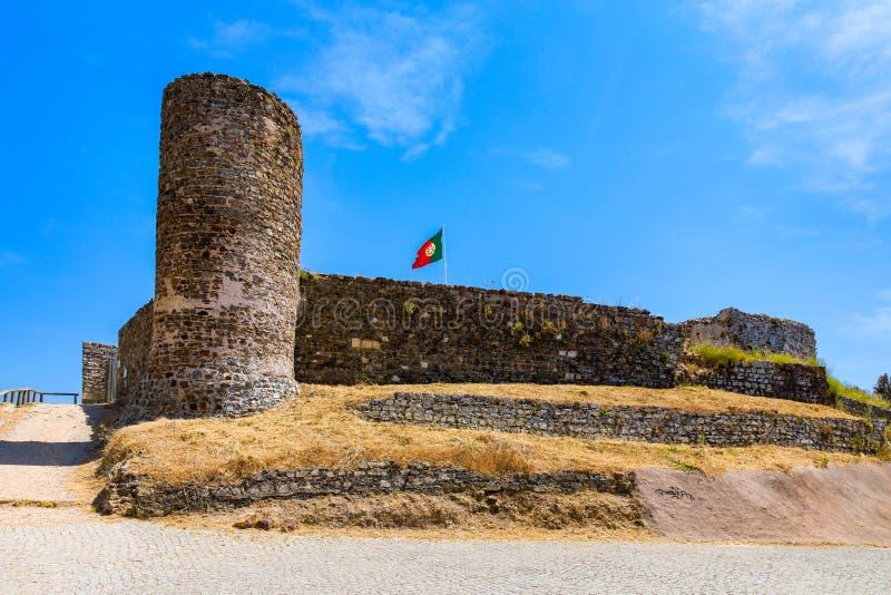 Ru?nas do castelo em Aljezur com ondula??o da bandeira portuguesa, o Algarve, Portugal O castelo de Aljezur, castelo lindo ?rabe  fotografia de stock royalty free