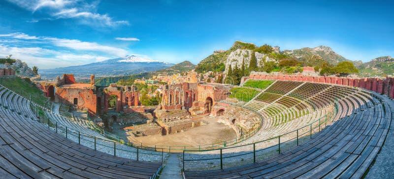 Ru?nas do teatro do grego cl?ssico no vulc?o de Taormina e de Etna no fundo fotografia de stock