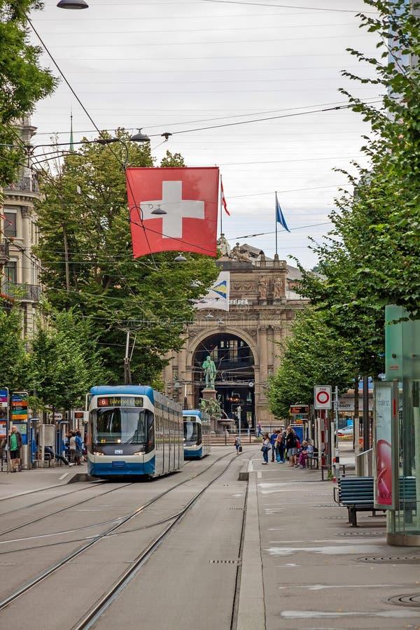Rua Bahnhofstrasse da compra de Zurique com a bandeira do bonde e do suíço foto de stock royalty free