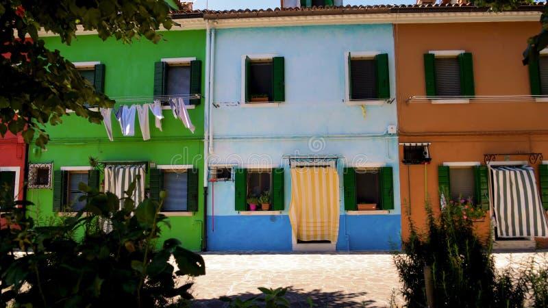 Rua colorida com casas coloridos, secagem da lavanderia no vento, plantas verdes foto de stock