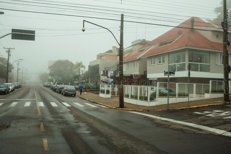 Rua com casas e carros estacionados em um dia nevado imagens de stock