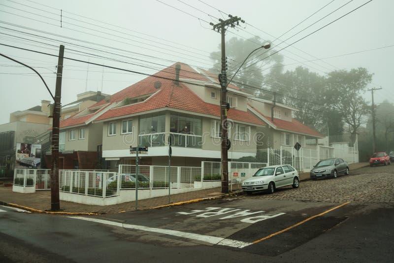 Rua com casas e carros estacionados em um dia nevado imagem de stock royalty free