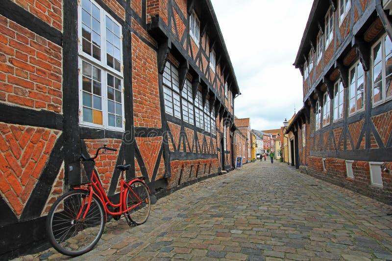A rua com casas velhas e o vintage bicycle, cidade real Ribe, Dinamarca imagens de stock