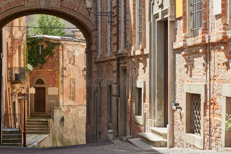 Rua com construções de tijolos vermelhos e construções antigas em um dia ensolarado em Mondovi, Itália fotos de stock royalty free