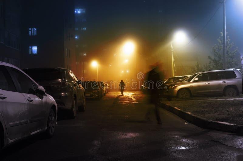 Rua com a silhueta misteriosa da névoa do homem e do ciclista imagem de stock