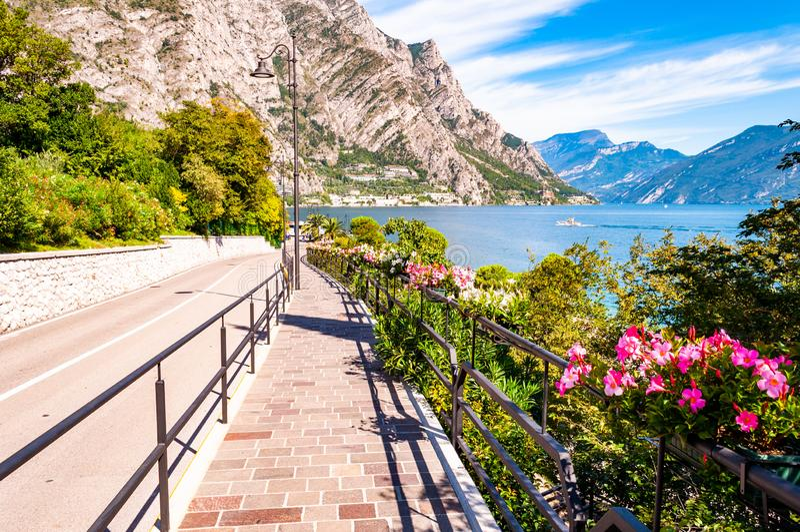 Rua Cozy, Limone Sul Garda, com calçada de pedra calcinante, flores florescentes em uma grade de metal, cultivando árvores com in imagem de stock royalty free