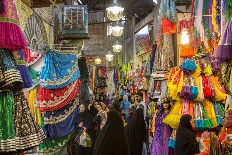 Rua da feira de Shiraz Vakil com as mulheres que verificam a roupa colorida tradicional e véus muçulmanos imagens de stock