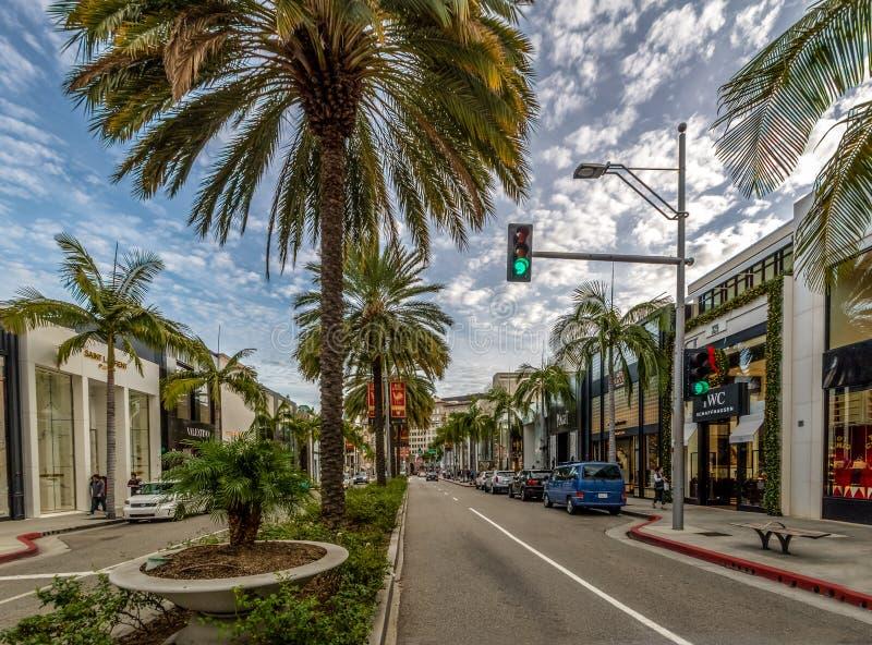 Rua da movimentação do rodeio com lojas e palmeiras em Beverly Hills - Los Angeles, Califórnia, EUA imagem de stock