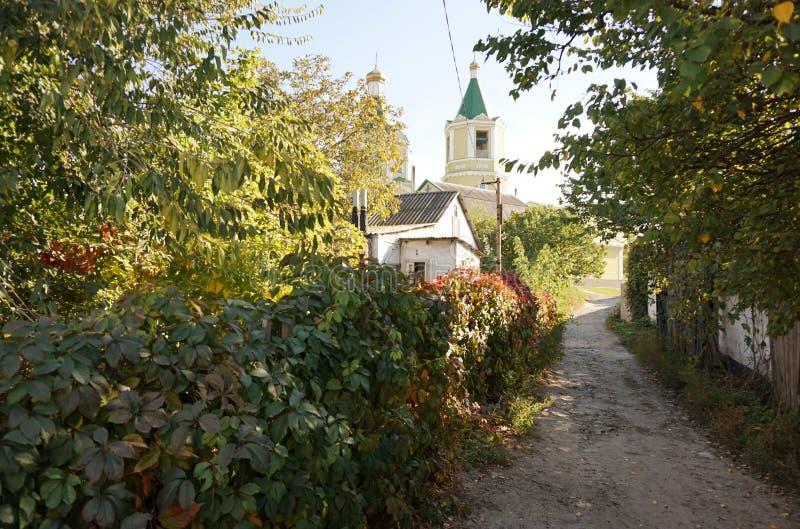 Rua da vila com uma casa pequena e as árvores do outono fotografia de stock royalty free