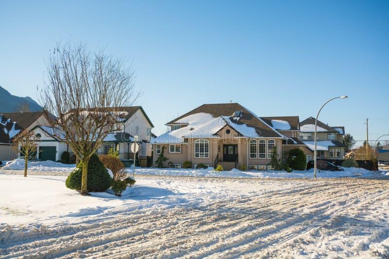 Rua de casas residenciais na neve no dia ensolarado do inverno fotografia de stock royalty free