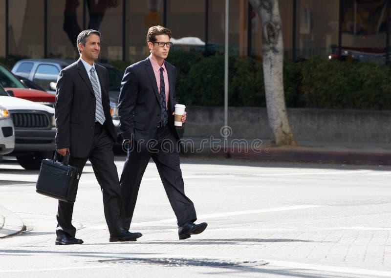Rua de Chatting Whilst Crossing de dois homens de negócios imagens de stock royalty free