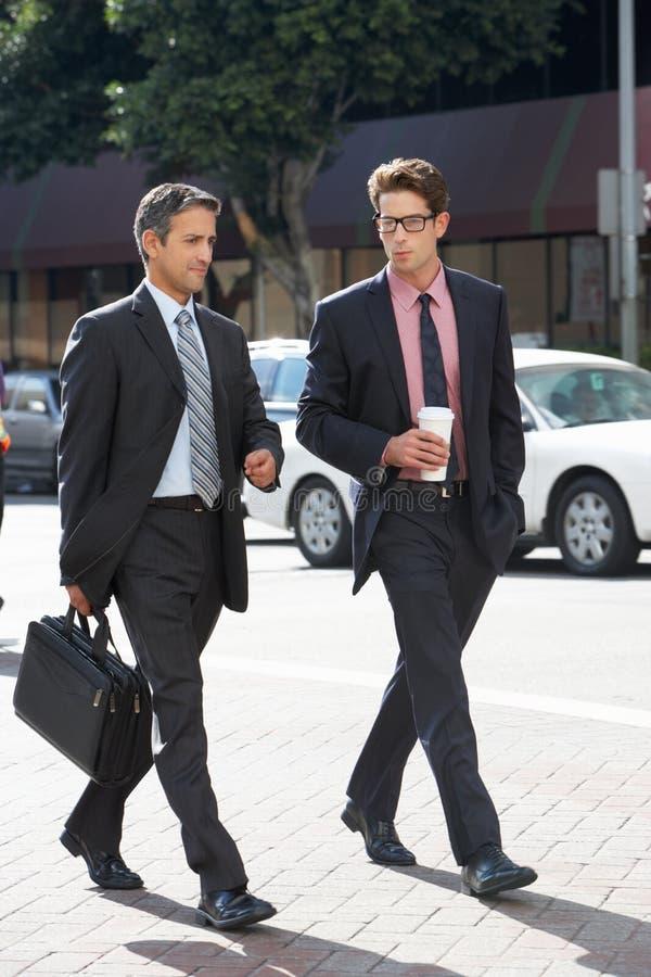 Rua de Chatting Whilst Crossing de dois homens de negócios fotografia de stock