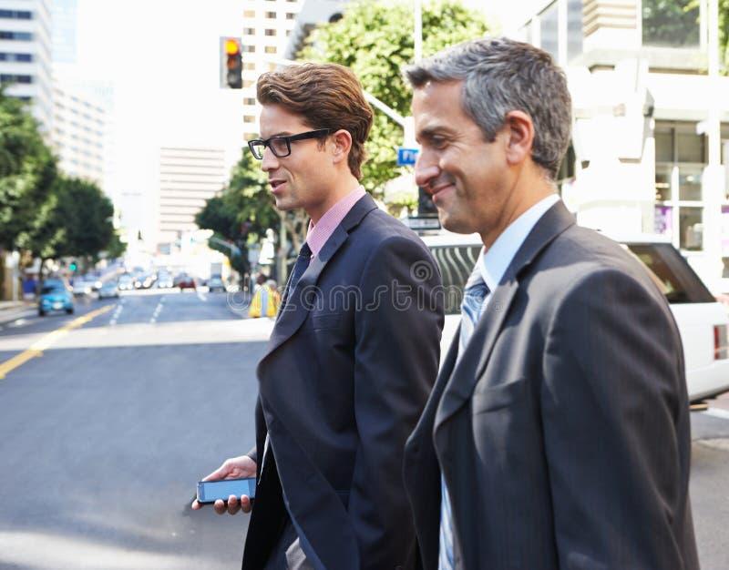 Rua de Chatting Whilst Crossing de dois homens de negócios foto de stock