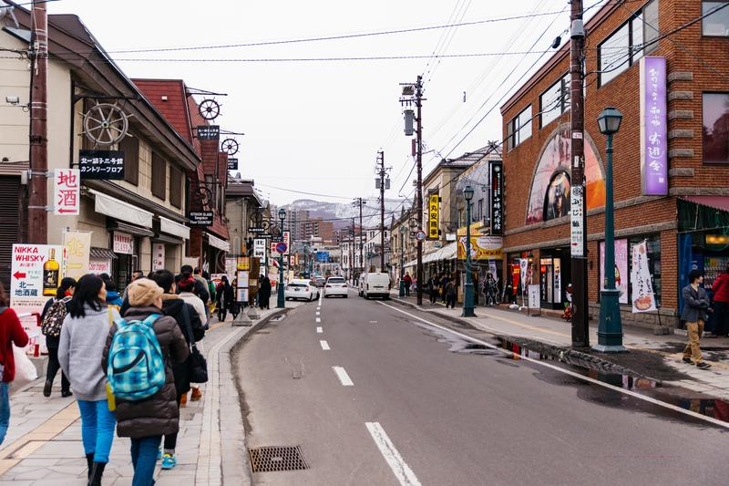 Rua de Otaru que junto com casas e café com a montanha no fundo no Hokkaido, Japão foto de stock