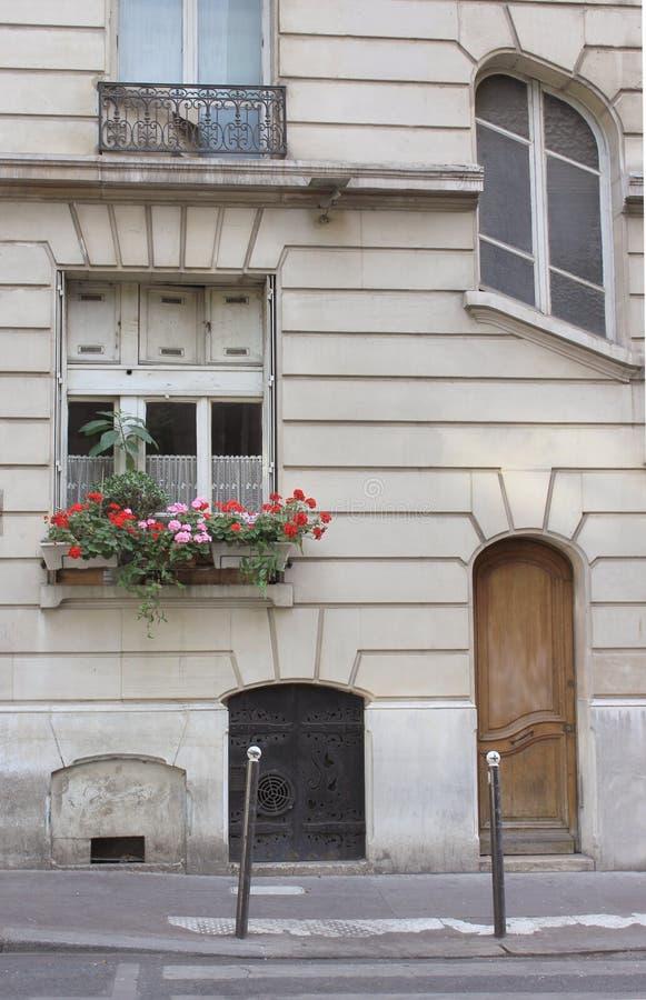 Rua de Paris no verão, no potenciômetro de flor, na porta e nas janelas imagens de stock