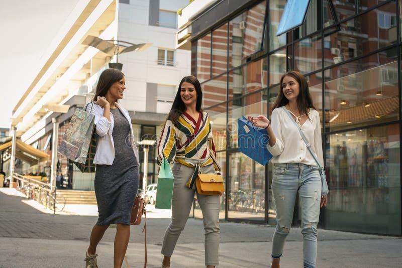 Rua de passeio da cidade de três jovens mulheres com sacos de compras fotos de stock royalty free