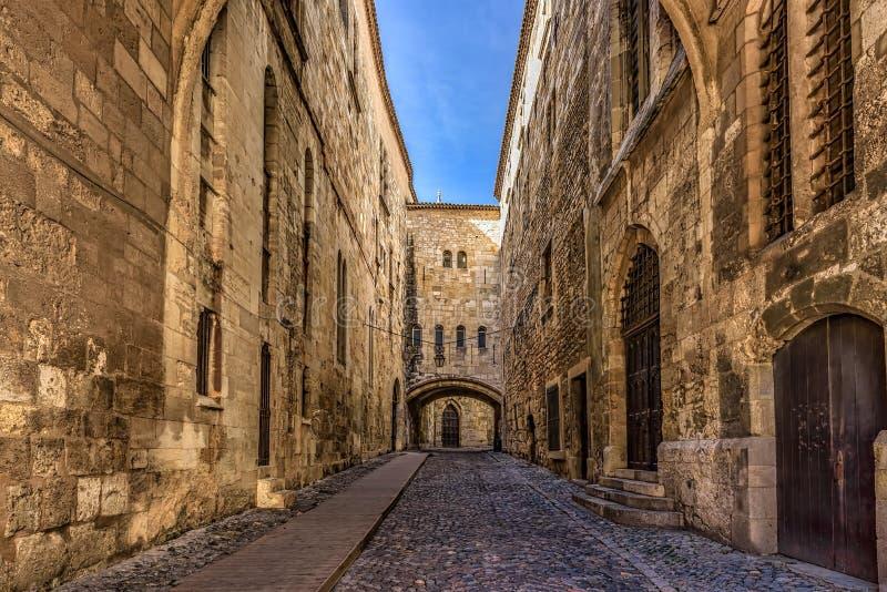 Rua de pedrinha entre paredes altas em uma cidade medieval fotografia de stock