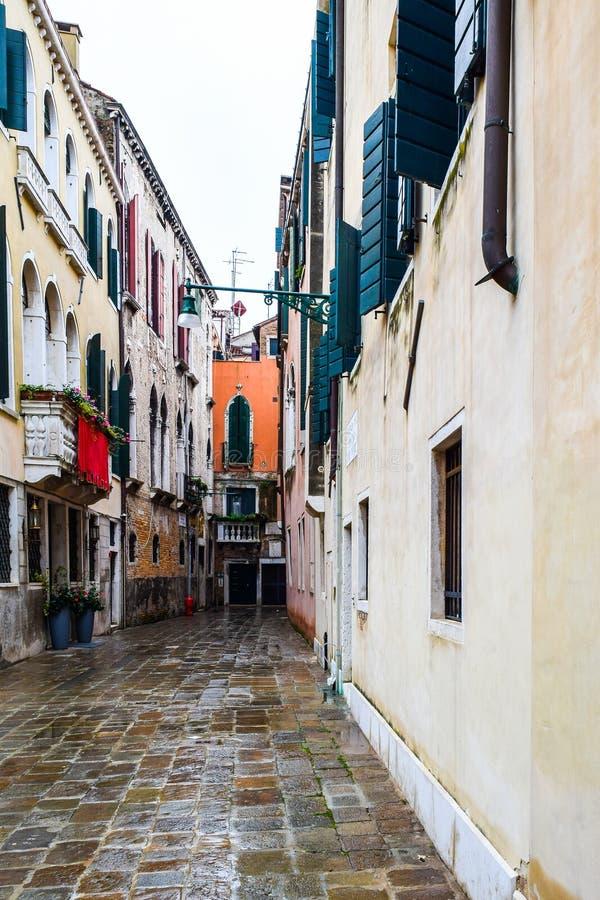 Rua de pedrinha tradicional e construções coloridas em Veneza, Itália foto de stock royalty free