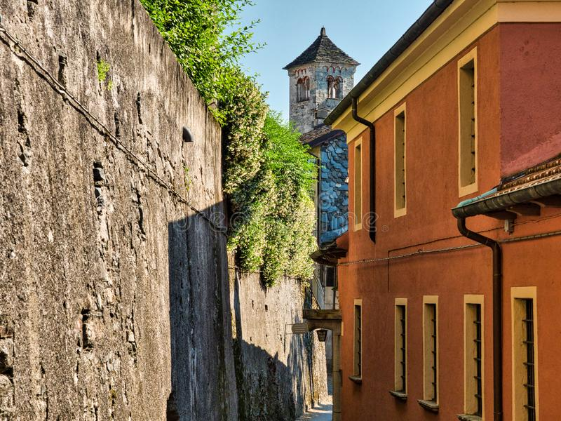 Rua desolada com através de e paredes de pedra no San GIulio Island no lago Orta Itália com a torre de sino de San Giulio Basilic foto de stock royalty free