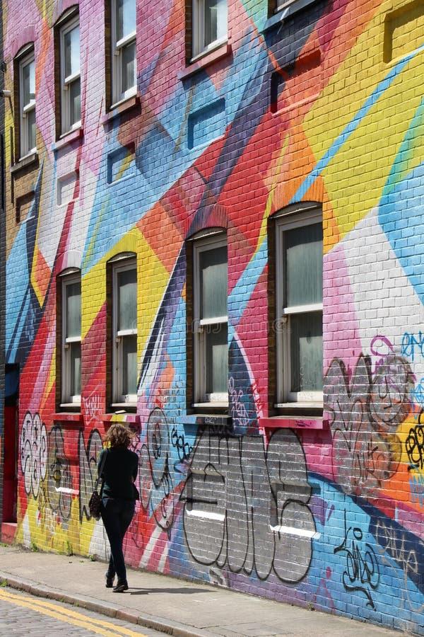 Rua dos grafittis com passeio da mulher foto de stock