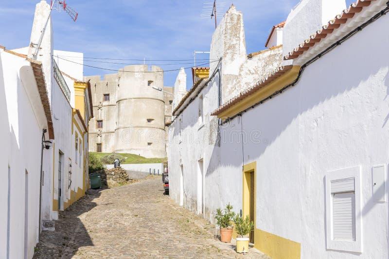 Rua e o castelo na vila de Evoramonte, a municipalidade de Estremoz, o Alentejo, Portugal foto de stock royalty free