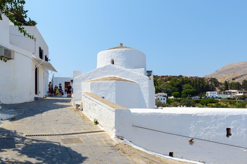 Rua estreita com as casas brancas na cidade de Lindos na ilha do Rodes, Grécia foto de stock