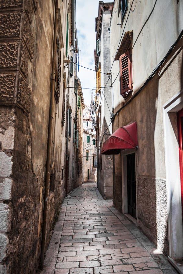 A rua estreita na cidade com as construções velhas que recuam na distância foto de stock royalty free