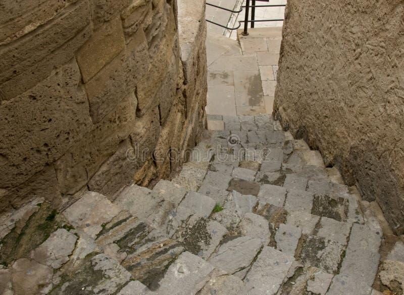 Rua estreita na cidade velha com a escadaria de pedra da pedra velha para baixo imagens de stock royalty free