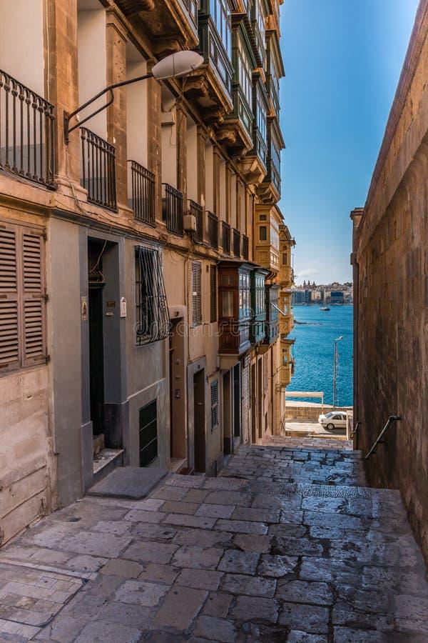Rua estreita que conduz ao mar em Malta imagem de stock royalty free