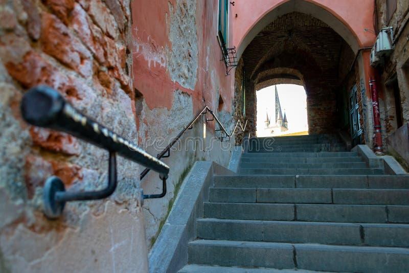 Rua estreita velha com as paredes de tijolo encarquilhados, as escadas do cimento e um corrimão preto do metal que aponta acima p foto de stock royalty free