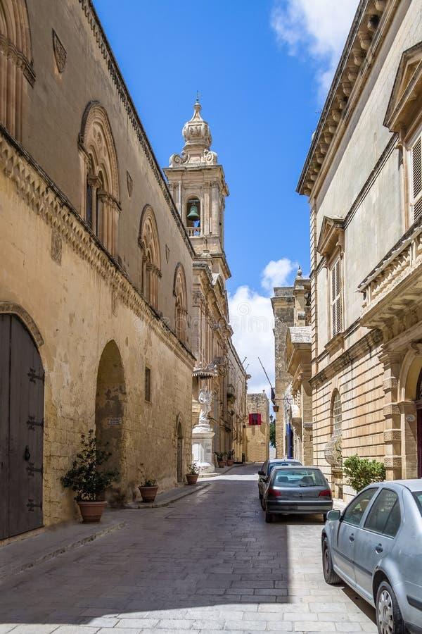 Rua estreita velha de Mdina com a torre de Bell carmelita da igreja - Mdina, Malta fotos de stock