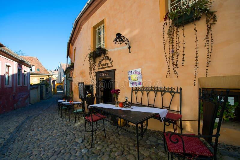 Rua medieval com a barra do café na cidade de Sighisoara foto de stock