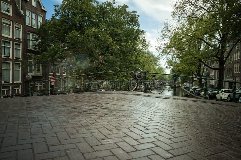 Rua molhada em Amsterdão em um canal do scneery imagem de stock royalty free